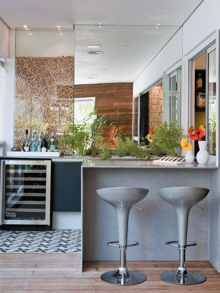 Varanda Gourmet compacta, na decoração um espelho que ajuda a dar amplitude ao ambiente.